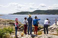 people standing on the shore of a fjord in Québec
