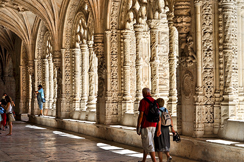 a couple walking past ornate stone carvings in a monastery in Lisbon