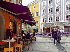 a couple walking past a cafe in Passau