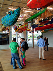 people standing under a boat display in a museum in Miami