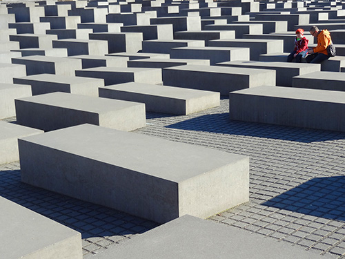 a couple sitting by a large memorial in Berlin