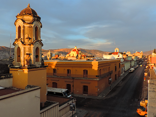 sun setting over buildings in an old Colonial city in Oaxaca