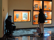 a woman looking at a display in a museum in Oaxaca