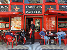 people sitting outside a  brightly painted red bar