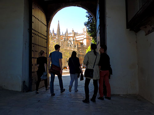 people walking through on large wooden door onto a plaza with old buildings in Seville