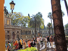 people walking by a wal in a formal garden in Seville