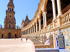 people walking along a brightly tiled colonade in Seville