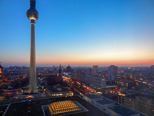 A tall television tower over a city at sunset in Berlin