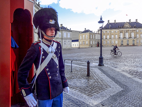 Guard in formal dress at his post outside a palace in Scandinavia