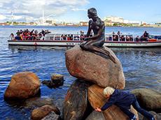 a tour boat passing Copenhagen's Little Mermaid in Scandinavia