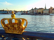 a golden crown on a bridge by a harbor in Scandinavia