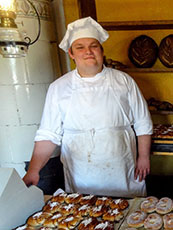 a chef standing behind a display of pasteries in Scandinavia