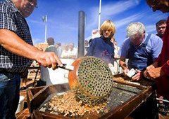 people cooking shrimp over an outdoor stove in European food festivals