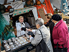 women buying fish off a boat dockside in European food festivals