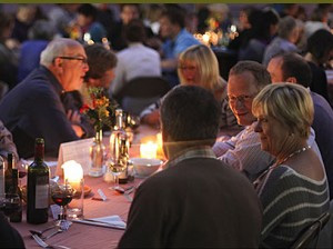 people at a candle-lit table in European food festivals