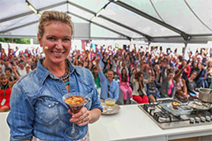 woman on stage in front of a crowd in European food festivals