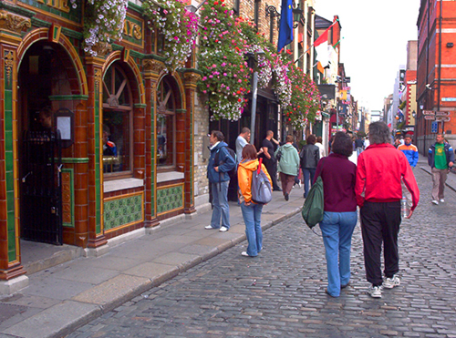 people walaaking along a cobblestone street with flowers on the buildings in Dublin