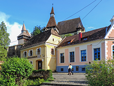 people walking by an old church and colorful buildings