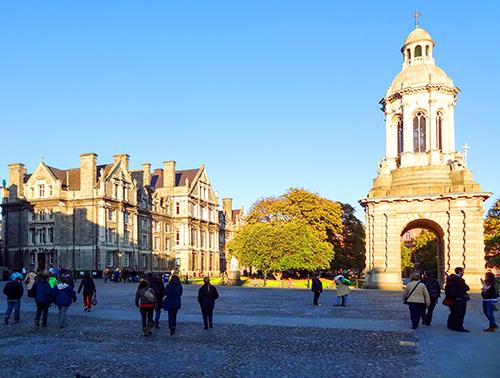 people walking on past old college bildings in Dublin