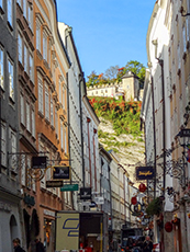view from a narrow street looinking up at a fortress on a hill in Salzburg