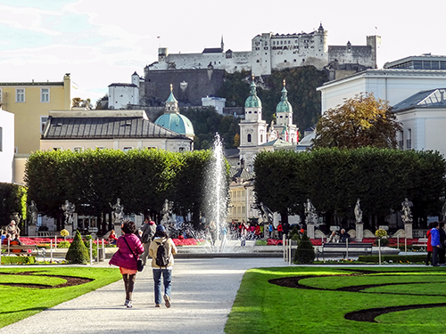 people walking in a park towards a fountain with an old vity in the distance in Salzburg