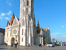 people standing in front of an old Gothic church in Budapest