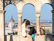a couple sitting in an archway with a church dome in the distance in Budapest