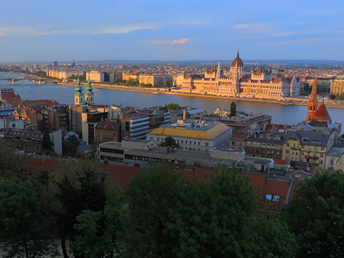 sunset on a river and an ornate Old World building in Budapest