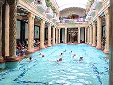 people in a swimming pool with ornate columns around them in Budapest