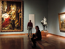people viewing a large painting in a museum in Budapest