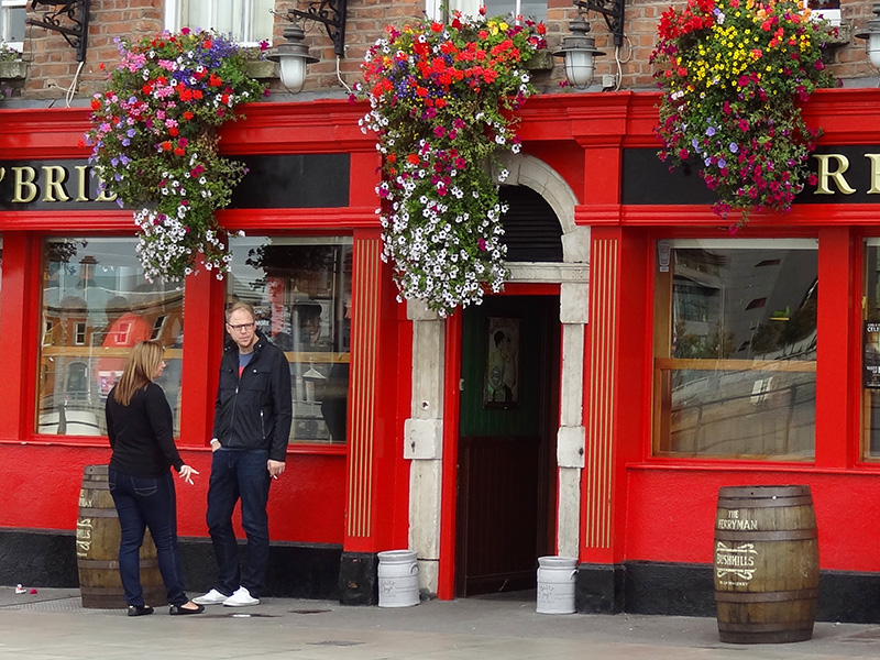 couple standing in front of a brightly painted red pub in Dublin