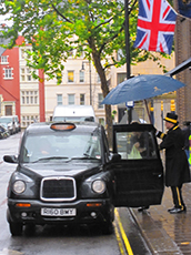 man holing umbrella for someone entering a taxi in London