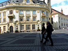 people walking \past a Baroque building in an old city in Romania
