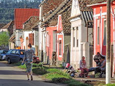 a small village with colorful houses with people sitting in front of them in Romania