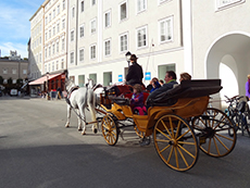 people in a horsedrawn carriage passing an old building in Salzburg