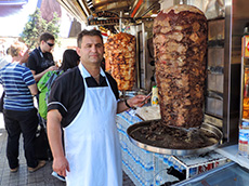 man standing by a large rotisserie in Istanbul