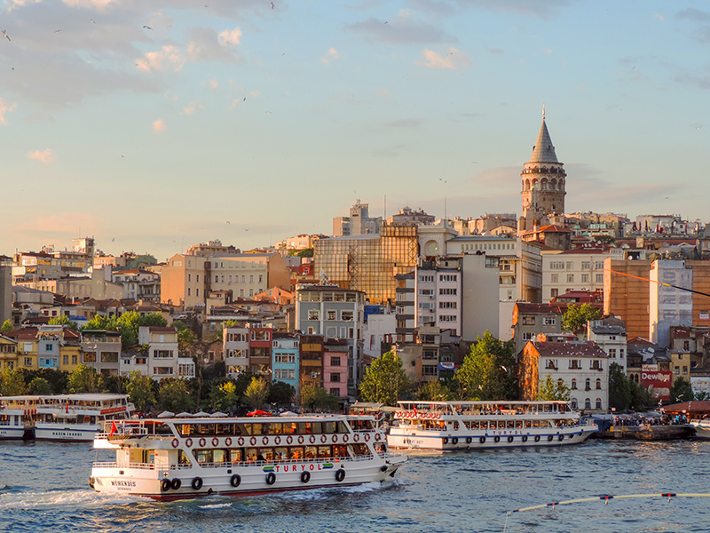a ferryboat going by a city in Istanbul