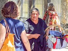 women walking past a street vendor in Segovia