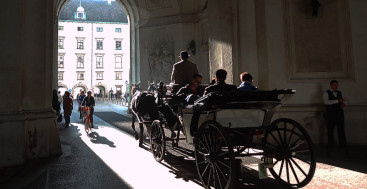 a horsedrawn carriage under an archway