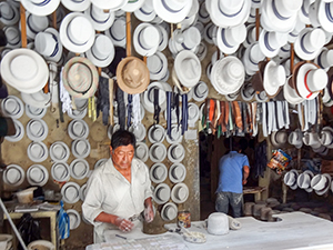 man standing under a large display of hats in Cuenca