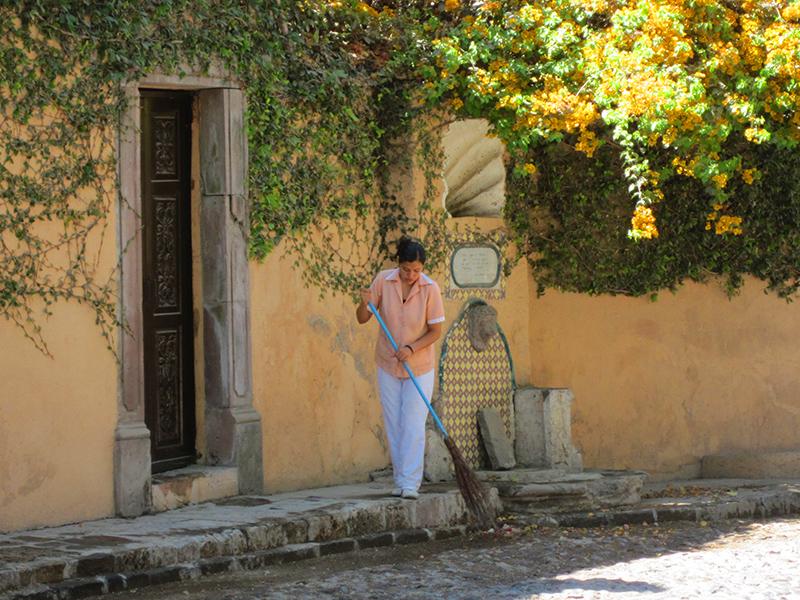 woman sweeping the sidewalk in San Miguel de Allende