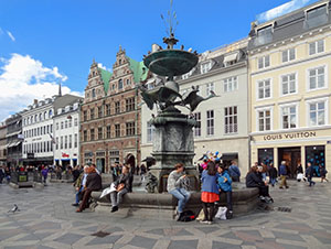 people sitting around a fountain by old buildings in Copenhagen