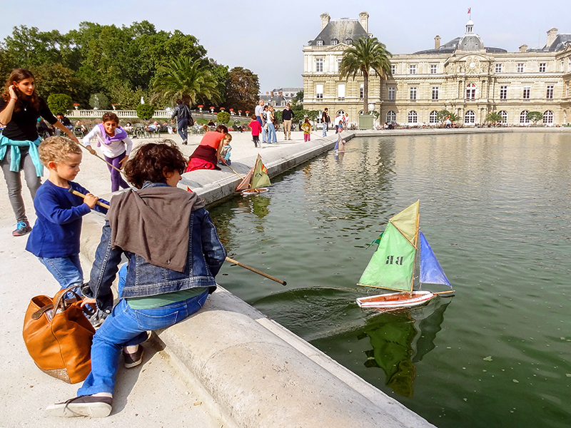 children playing with sailboats in a pond in Europe