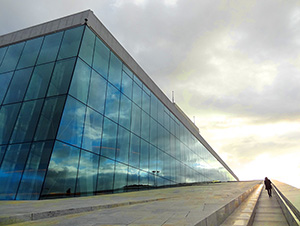 person walking alongside a large glass building in Oslo