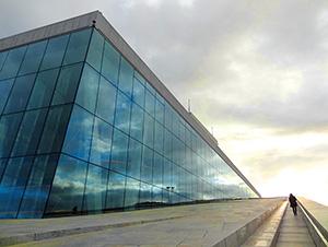 person walking alongside a large glass building in Oslo