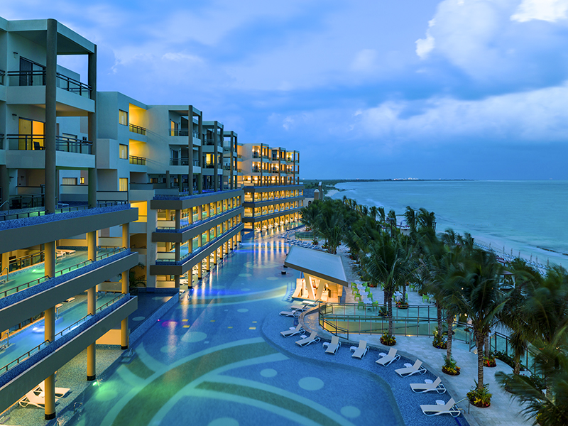 a hotel pool in the evening at a Riviera Maya hotel