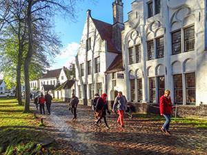 people walking by an old building Bruges, Belgium
