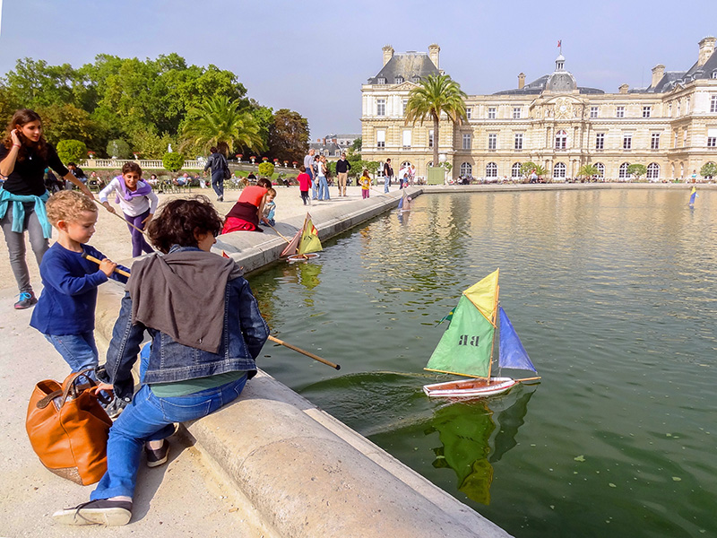 boy sailing a boat on a pond in Luxembourg Gardens, one of the top 10 places in Paris