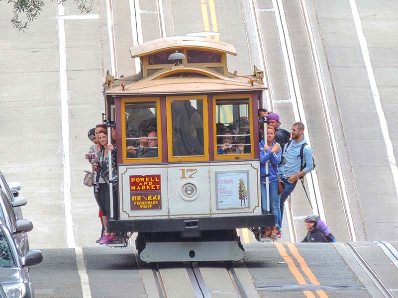 people on a san francisco cable car