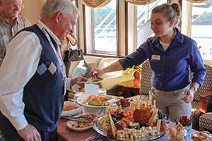 people being served food aboard Queen of the Mississippi